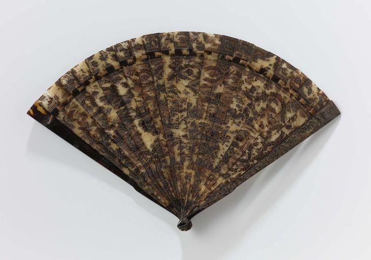 Huchong | Brisé fan, Huchong, c. 1800 - c. 1825 | Brisé-waaier van schildpad, ajour en in reliëf gesneden met een Chinees berg-en rotslandschap, tempels en huizen De achterkant van de waaier is niet in reliëf, maar glad. Langs de buitenrand van de benen vierkanten waarin een bloem. Montuur van 23 aaneengesloten benen, waarin centraal een ovaal medaillon met bloemtakken. Rondom de naturalistische voorstelling randen met guirlandes en vierpassen. Handdeel met ronde schouder. Metalen sluitpin…