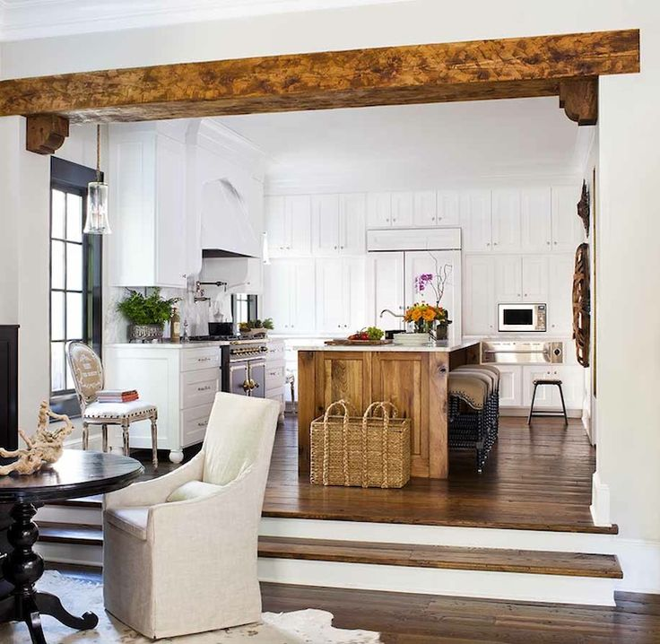 Kitchen opens to sunken dining room with rustic wood beam with corbels featuring glossy black pedestal table with natural linen slipcovered ...