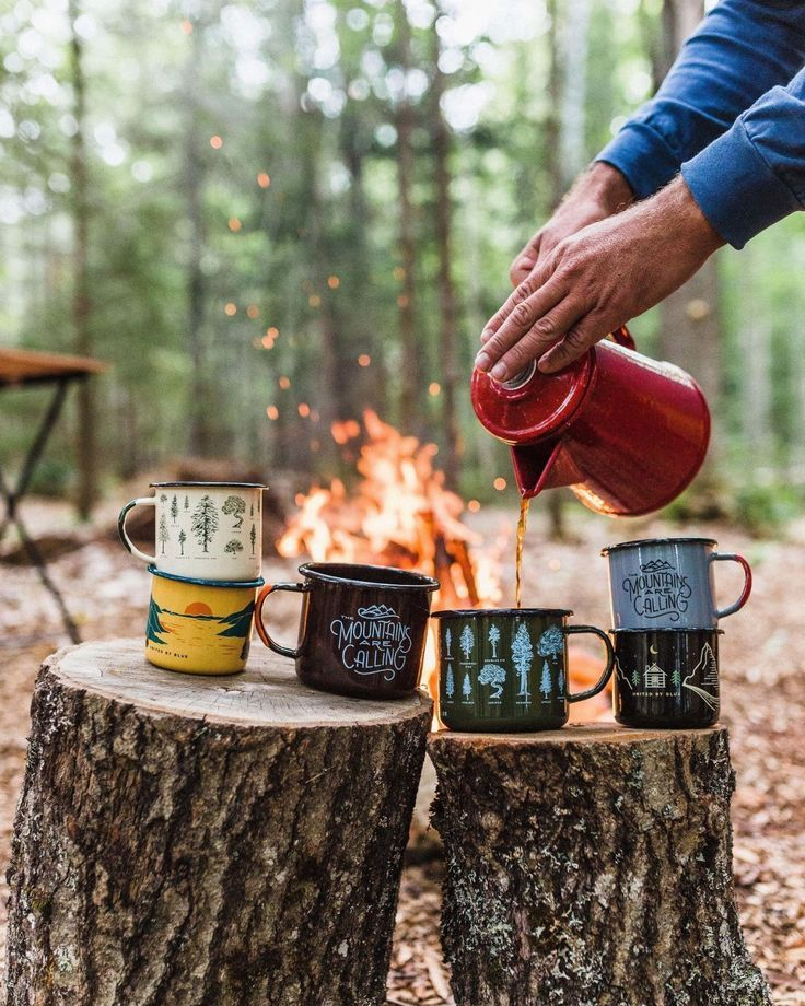 Good views, good brews. colorful tin camping mugs, french press coffee pot with a bonfire in the forest background