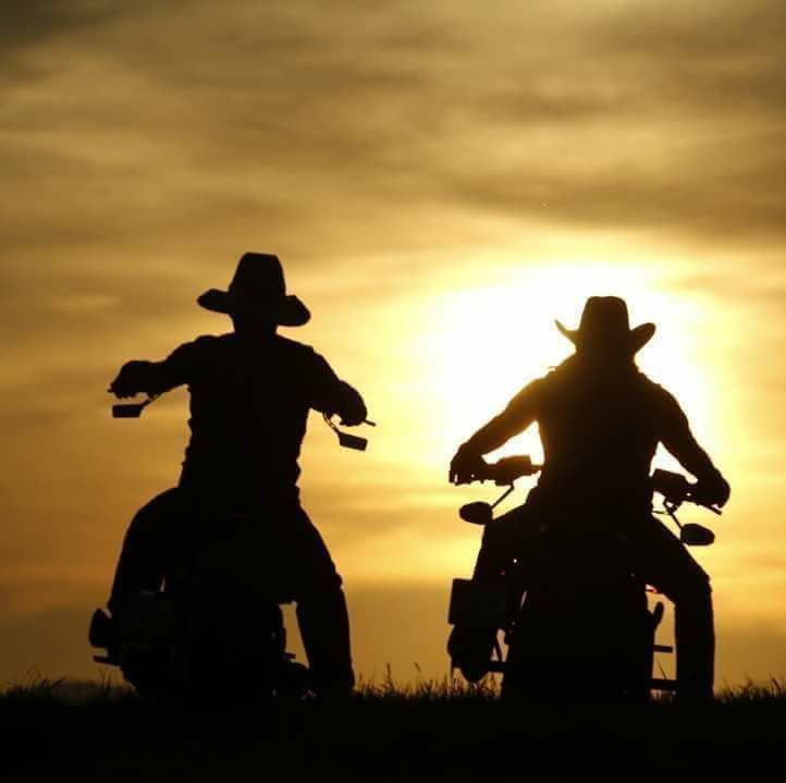 Motorcycle Riders In Cowboy Hats Riding Into The Sunset