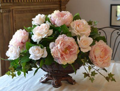 Add beauty without a lot of cost to your home. This classic design will soften a dark dining room with realistic looking pink peonies and life-like roses used to create this masterpiece. Arranged in a resin vase and can be custom made to match your decor