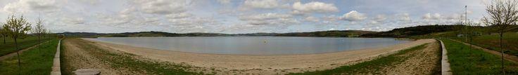 Panorámica dun lago artificial, As Pontes, A Coruña. Este lago creouse a raíz dos traballos de recuperación e rexeneración damina a ceo abertoque ocupaba o lugar do lago, da que se extraíalignitopara abastecer á Central Térmica de Pontes de García Rodríguez.   O lago creado por Endesa para encher o oco da mina de Pontes finalizou en abril do 2012. Ten unhas dimensións de 5kmde largo e unha profundidade máxima de 206m. Para enchelo, empleouse as augas do río Eume, que pasa pola…