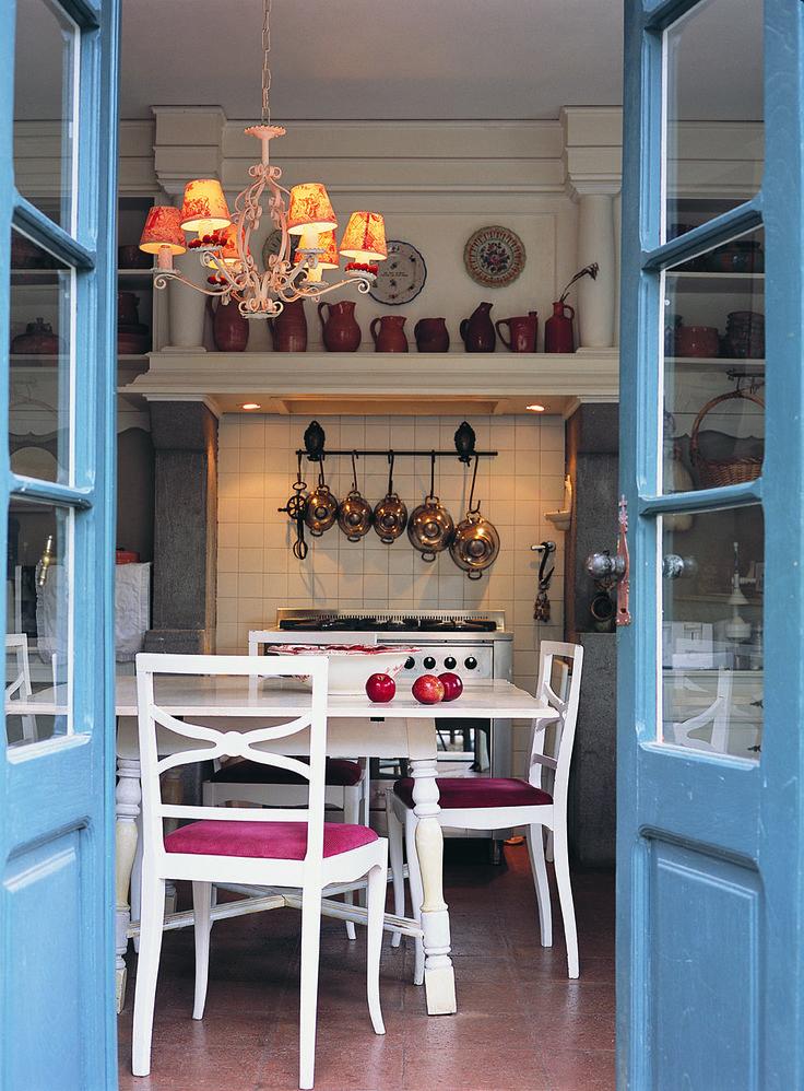 Cocina de una casa en Córdoba con ollas de cobre, jarras de barro cocido, vajilla de cerámica esmaltada, canastos y una araña con pantallas de Toile de Jouy.