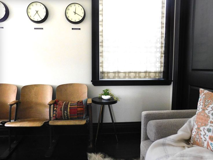 midcentury clocks, vintage theater seats and Room and Board daybed in bright and modern office area