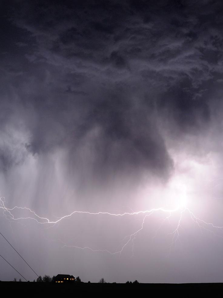 Un rayo golpea fuera de las nubes de una lluvia intensa por encima de una casa de cresta en las ondulantes colinas de las Montañas Azules, durante una tormenta la noche que pasa al este de Walla Walla, Washington (Matthew Zimmerman/AP)