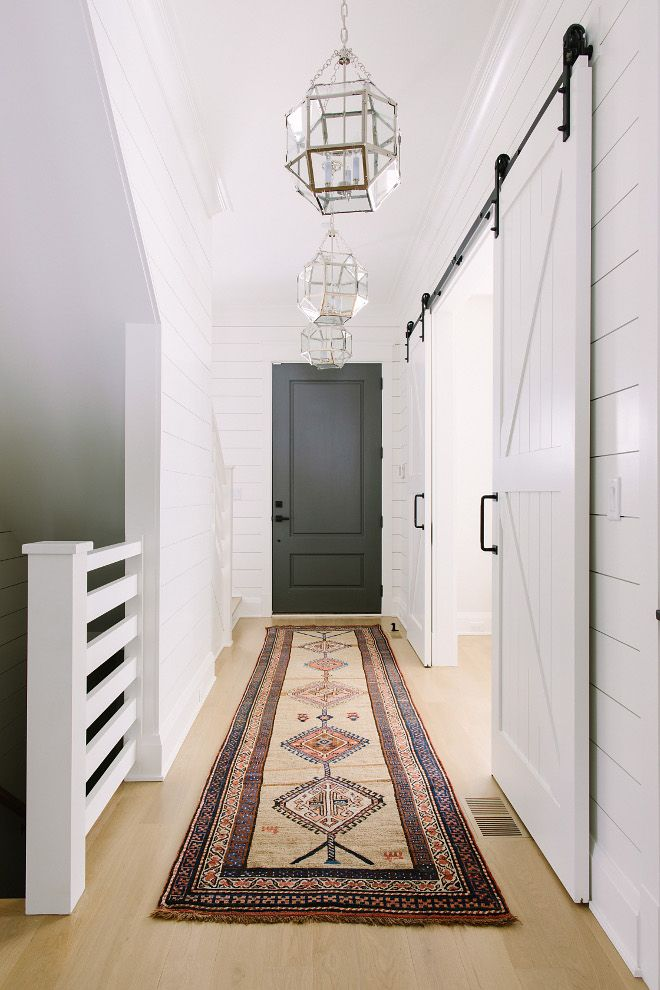 Farmhouse Hallway with bleached hardwood floors, shiplap paneling, vintage kilim runner, grey sliding barn doors and Visual Comfort Suzanne Kasler Morris Lantern Light Fixtures | Kate Marker Interiors - Modern Farmhouse
