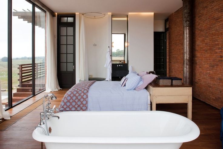 chambre à coucher avec baignoire, salle de bains attenante, parquet en bois et revêtement mural brique rouge