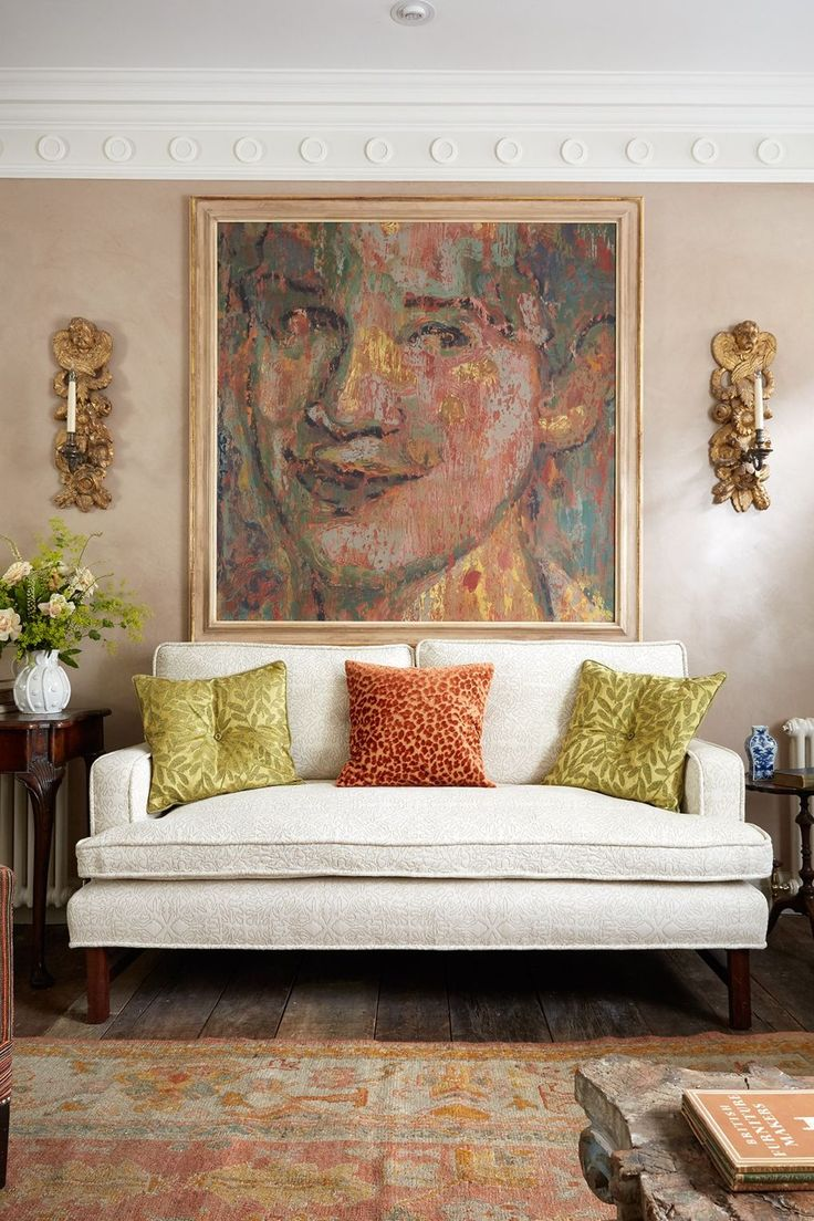 The colours of the bold portraiture over the sofa match the multicoloured cushions.