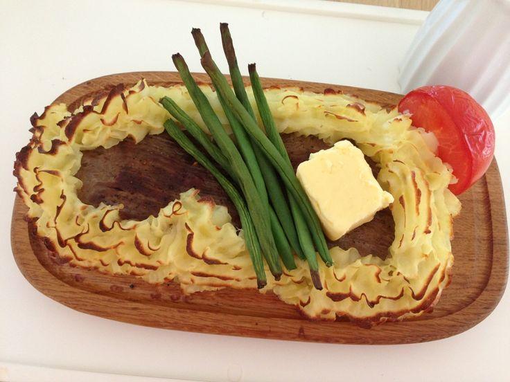 Plankebøf, den traditionelle udgave, som vi husker retten fra restaurant-besøg. Bøf med kartoffelmos, bagt tomat og friske bønner, hvidløgssmør på toppen og sauce til.