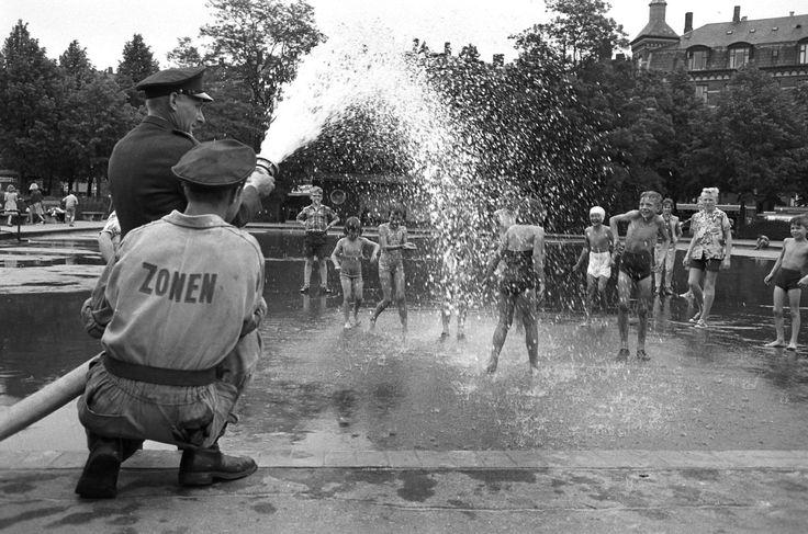 Redningskorpset Zonen fylder soppebassinet i Nørrebroparken med vand.; Men from The Salvage Corps Zonen hoses water to the water reservoir in Noerrebro ( Nørrebro) park.;