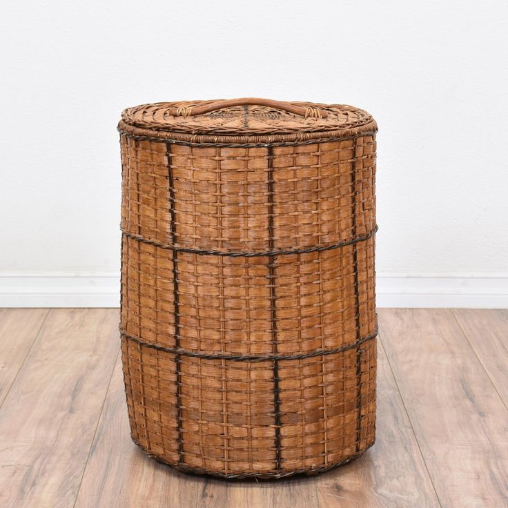 This woven hamper basket is featured in a synthetic wicker with a honey-brown finish. This lightweight laundry basket has a handle, removable lid, and plenty of storage space. Perfect for storing clothes until laundry day! #tropical #decor #decorativeaccents #sandiegovintage #vintagefurniture