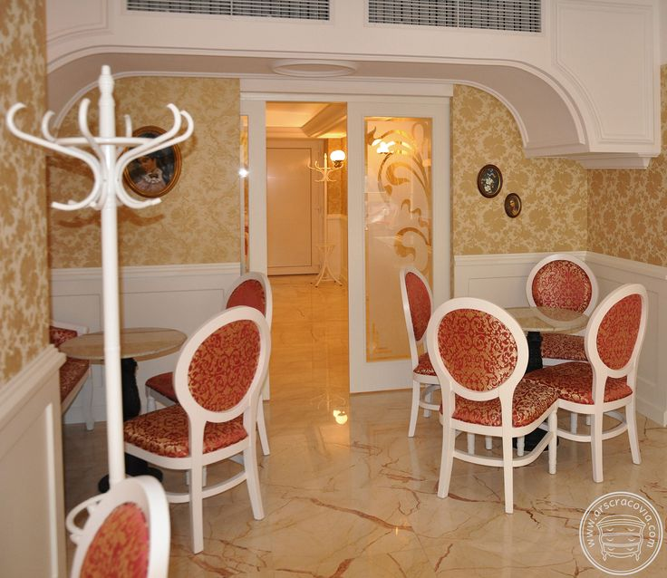 Stylizowane boazerie z wbudowanymi drzwiami przesuwnymi we wnętrzu kawiarni, wykonane z lakierowanego mdf-u.