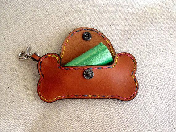 Hueso, para llevar las bolsitas de nuestra mascota, realizado artesanalmente, cosido a mano en vaquetilla. Tiene un pequeño mosquetón para