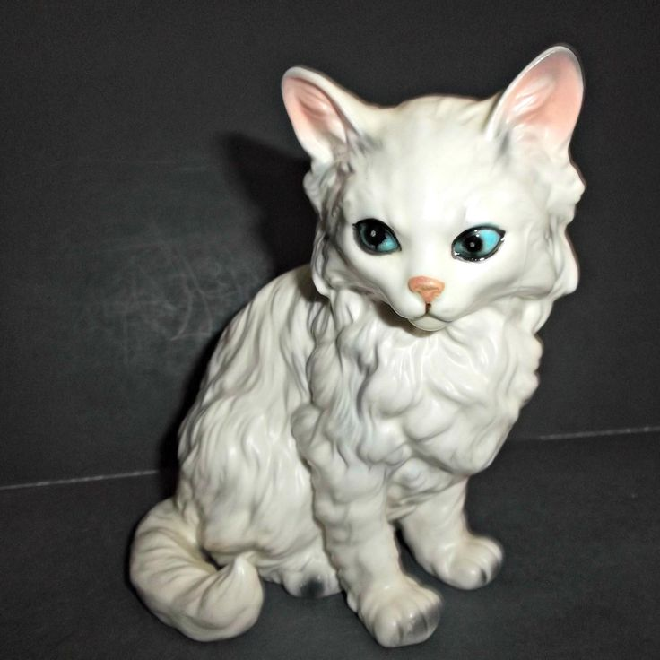 A vintage Lefton cat, kitten, figurine. White with gray streaks, paws and ear tips.  Inside ears are pink and eyes are a bright blue with black