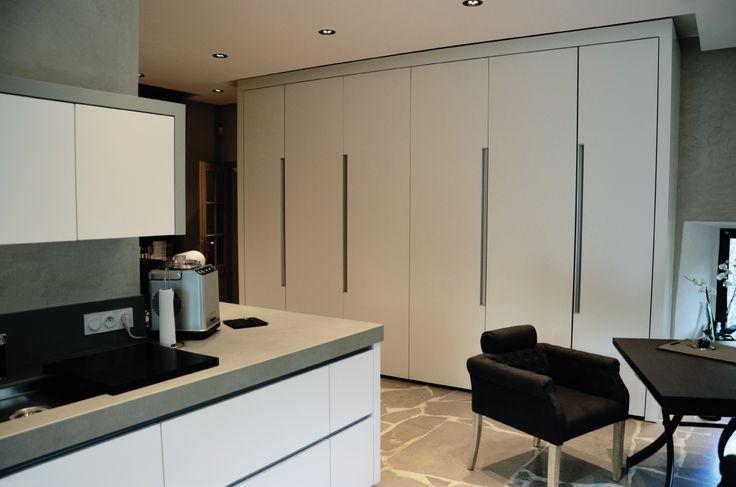 Une cuisine moderne au cœur d'une chaumière - minimaliste, design contemporain, façade prise de main laqué blanc, jambages, crédences et plan de travail en céramique gris, mur de rangement caché