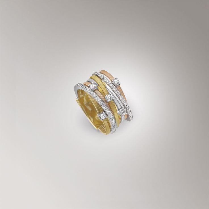 Marco Bicego  Goa AG277 B2 Anello a sette fili in oro 18 carati nei colori giallo, bianco e rosa, realizzato a mano con la tecnica della Corda di chitarra.  Questo gioiello monta 0,21 Carati di Diamanti taglio brillante.