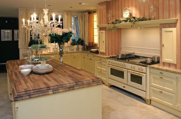 Klassieke, landelijke keuken in een gebroken witte kleur. Het werkblad op het kookeiland heeft een houten look, wat het landelijke en warmte nog meer naar voor brengt.