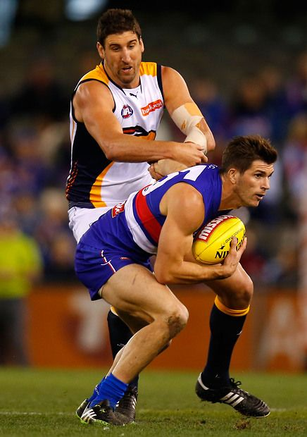 Koby Stevens of the Bulldogs fends off Dean Cox of the Eagles during the 2013 AFL Round 18 match between the Western Bulldogs and the West Coast Eagles