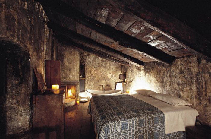 Rustic bedroom in hotel in Italy with aged wood beam ceiling and crochet bedspread