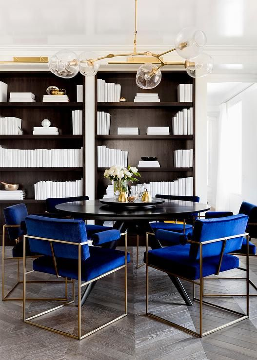 Contemporary den features a brass and brass modular chandelier over a black round table lined with deep blue velvet chairs atop wood herringbone floor placed in front of recessed bookcases filled with all white books.