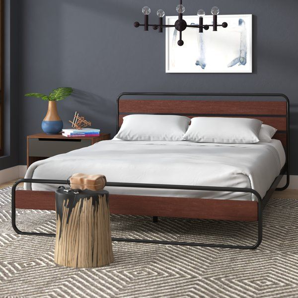 An approachable contemporary update on a midcentury modern design, this streamlined platform bed anchors any master suite or guest room in understated style. Founded on a black tubular steel frame, the headboard and footboard feature pine wood panels for a chic mixed material construction, while the low-profile side rails and strong wooden slats support your preferred mattress. Rounding out the design, center supports provide sturdy structure while offering 8'' of clearance for valuable…