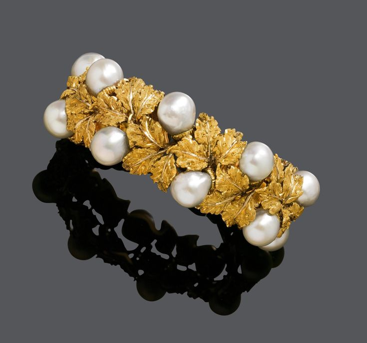 PEARL AND GOLD BANGLE, BY M. BUCCELLATI. Yellow gold 750, 76g. Composed of textured gold leaf motifs and as fruits 10 baroque South Sea cultured pearls of ca. 9,5–10 mm Ø. Signed M. Buccellati. Ca. 5,2 x 4,2 cm.