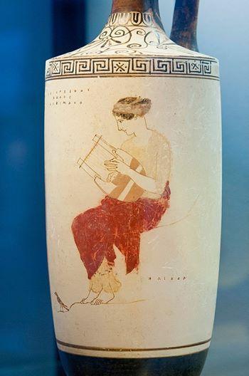 Lekythos a fondo bianco di produzione attica attribuita al Pittore di Achille. E' raffigurata una musa, forse Erato, seduta su una roccia mentre suona la lira; un uccellino sta ai suoi piedi. Antikensammlungen di Monaco. V secolo a.C.
