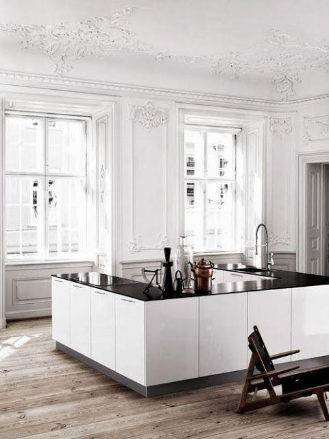 Cuisine centrale blanche en U par Kvik. Le cadre d'un appartement type haussmannien met la cuisine en valeur.