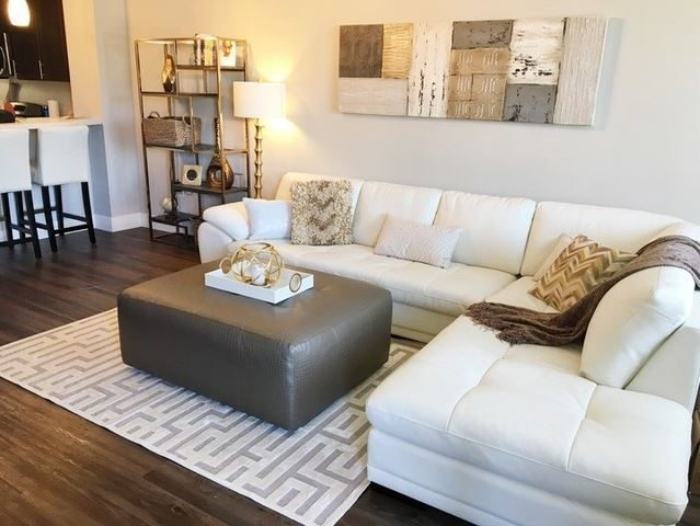 Let the lights shine on this glamours home. A white, leather sectional offers the perfect contrast to dark, wooden floor. Add a rug with some fine lines, wall art for texture, and your home will be dressed to impress. #LivingSpaces #myLivingSpaces #glam #inspiration