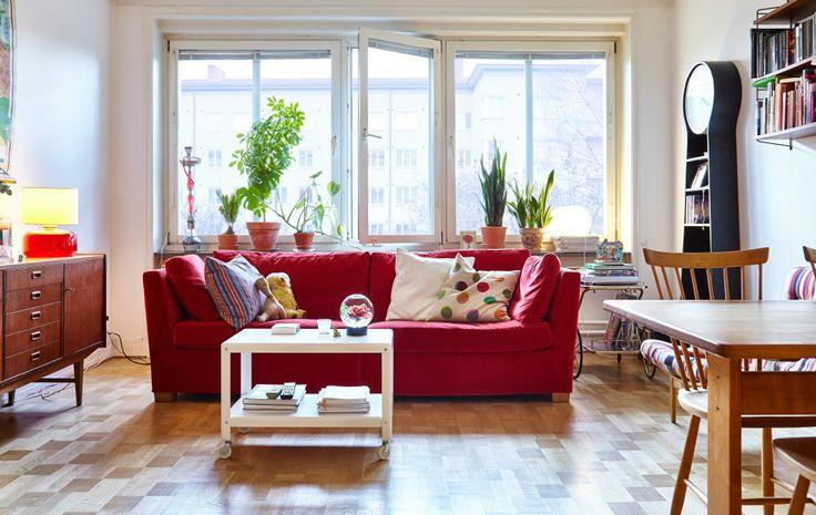 窓際の素晴らしい場所にモダンな赤のソファ、その両側にサイドボードやバーカート、ダイニングテーブルなどのレトロ調の家具がコーディネートされた、ウッドフロアのリビングルーム