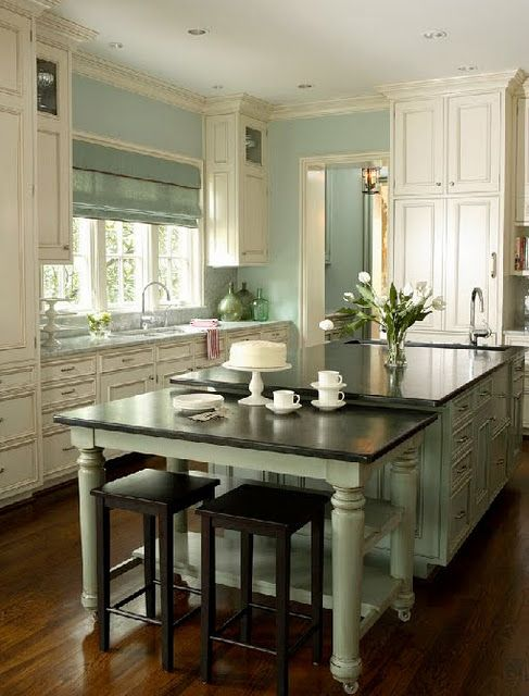 Kitchen with turned leg island, white cabinets, and robins egg blue walls.
