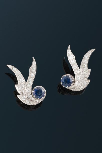 Paire de boucles d'oreilles en or gris 18 K (750 °/°°) stylisant deux volutes serties de diamants taille ancienne terminées par un saphir.  Poids brut : 9,9 gr. - Millon - 06/07/2017