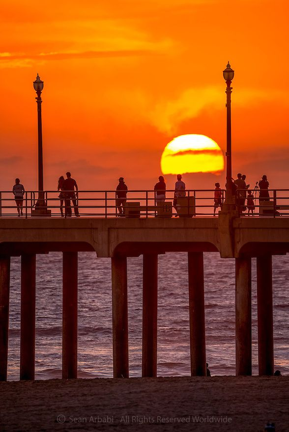 """USA: California: Orange County: Huntington Beach (""""Surf City USA""""): The sun sets over the beach and Pacific Ocean as visitors, vacationers, and locals walk along the 1,850 foot Huntington Beach Pier near Highway 1/ Pacific Coast Highway © Sean Arbabi 