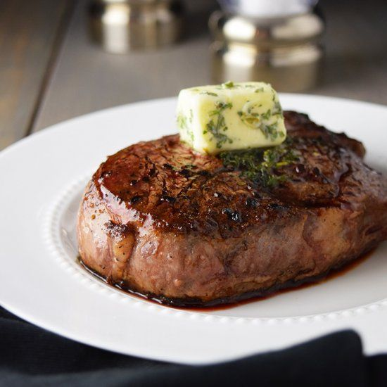 Filet Mignon seared on a cast iron skillet and finished in the oven. Crisp on the outside and medium rare on the inside. Topped with butter.