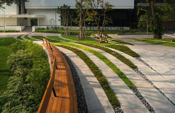 Custom bench seating follows the theme of the overall design and provides a touch of color and highlight for the primary, bounding curve. Image courtesy of Landscape Architects of Bangkok