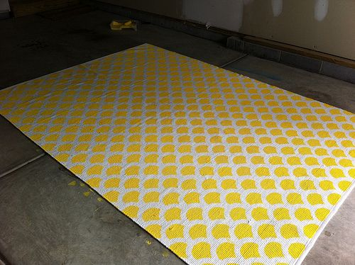 Buy a cheap rug and paint your pattern. Pretty big project, but doesn't seem difficult.