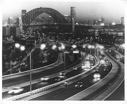Warringah Expressway, a night time view of Sydney, with the unusual outline of the world famous Harbour Bridge looming in the background, 1968. Photograph by Helmut Gritscher.