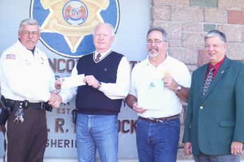The Electrical Connection recently donated $3,000 to the St. Francois County 'Shop with a Cop' program to benefit needy families and children. On hand for the Dec. 12, 2006 presentation ceremony (from left) Sheriff Dan Bullock; Danny Miller, owner of Total Electric; Deputy Sheriff Rodney Harris; and David Shaw, representing the St. Louis Chapter, National Electrical Contractors Association.