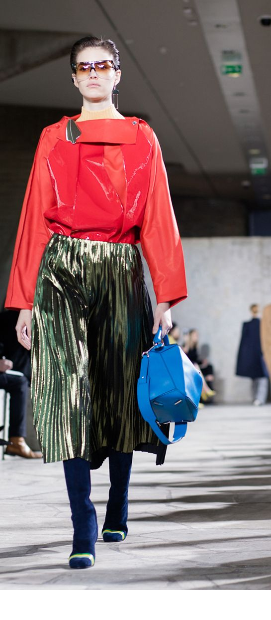 LOEWE Autumn Winter 15 look 19. Panelled layer top-patent suede-red / Skin turtle nack sweater-wool-almond / Pleated skirt silk-triacetate-gold / Filipa sunglasses-acetate-havana-transparent / Ibiza earring silver-rhodium / Small leaf earring-silver-black / Column ring boots-suede-nappa-navy blue-multicolor / Puzzle large bag-classic calf-turquoise