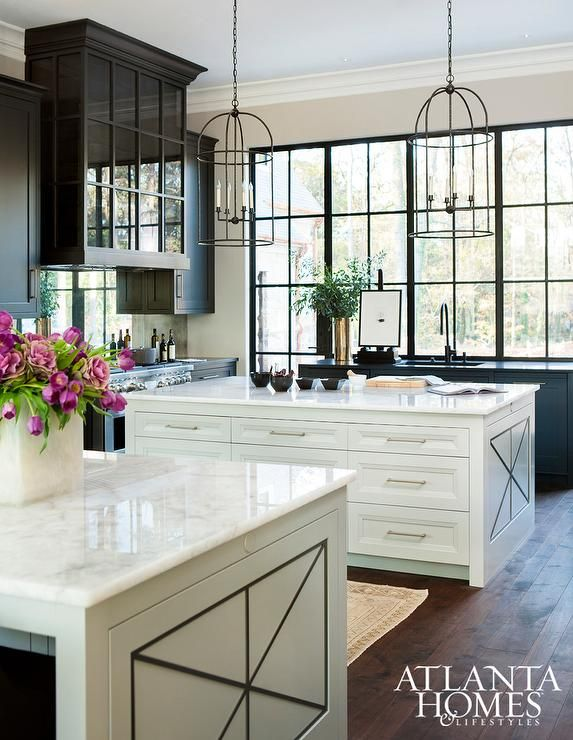 White and black kitchen features a pair of iron cage lanterns illuminating a white kitchen island fitted with plenty of drawers topped with white quartzite placed directly in front of a secondary kitchen island.