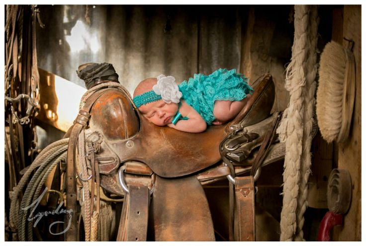 New Mexico Portrait Photography, Newborn baby girl pictures on her daddy's saddle. First horseback ride.