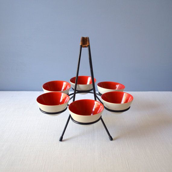 Gorgeous black metal stand with rattan wrapped handle with 6 porcelain bowls glazed in a bright and shiny red. Produced by Eslau of Denmark, a family owned ceramic company stablished in 1948, which in the 1960s invited artists like Jens Quistgaard and Niels Refsgaard to collaborate with them.  This difficult to find piece dates from the same era, and it features many of the design sensibilities of modernist design.  All pieces are in beautiful vintage condition with no damage. Metal stand…