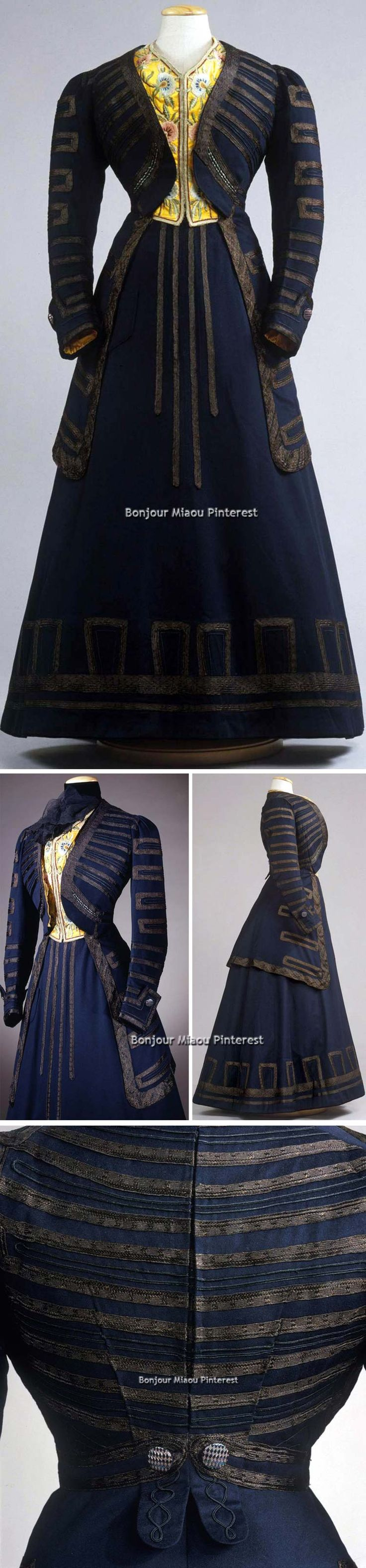 Walking dress, Mlle. Amalie Wallemien, Vienna, ca. 1908. Blue cloth with applications of brown silk braid. V-necked frock-style coat with long sleeves with high cuffs, lined in ivory linen, white cotton, & yellow silk. Faux vest in yellow taffeta, embroidered with floral polychrome. Flared skirt with patch pocket on right side, rear hooks. Balayeuse of blue velvet ribbon under skirt. Galleria del Costume di Palazzo Pitti via Europeana Fashion