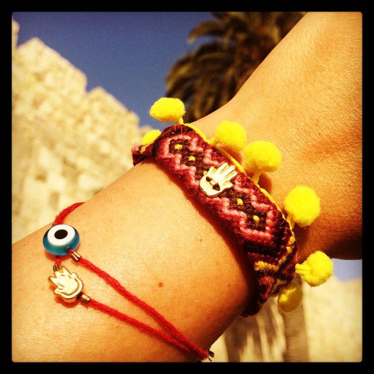 Our #danalevy mini hamsa hand charm midi pom pom friendship bracelets & hamsa and evil eye red string bracelets are shining in the midday sun at Jaffa gate, Jerusalem