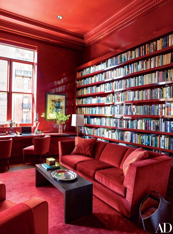 Lacquered bookshelves make a dramatic statement in the all-red library.