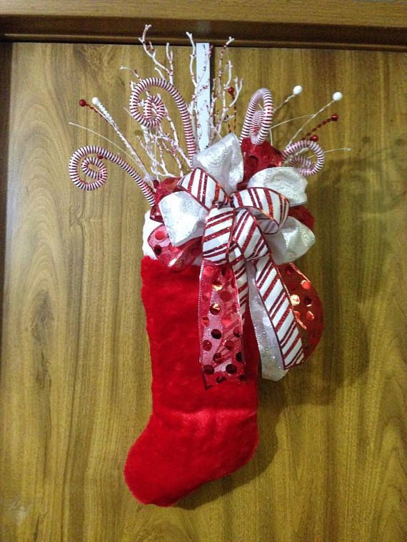For those who think outside the box, this is a different take on the traditional Christmas stocking. It would definitely look great on any door, wall or mantle. If hanging outdoors, please be sure to protect it from the elements This plush stocking is filled with assorted Christmas picks and a wired ribbon multi-loop bow. May vary slightly from picture. Makes a great gift. This door hanger measures approx. 23 x 15 x 6 and is boxed for immediate shipment. Since the ribbons are wire-edged, ...