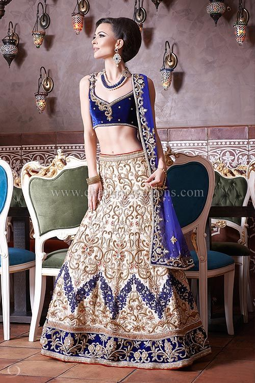 Bridal Lenghas - Champagne gold bridal lengha with a royal blue velvet blouse and contrasting blue embroidery on the skirt. Ideal for a wedding reception.
