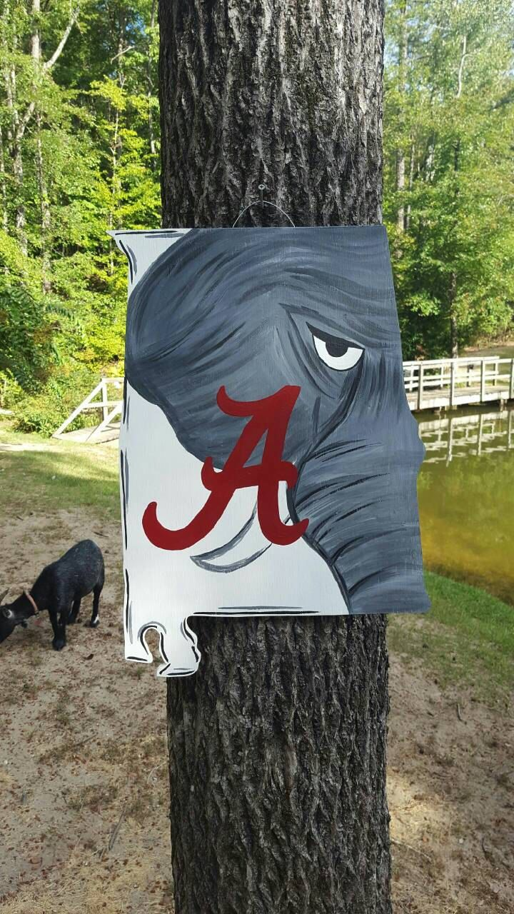 Roll Tide!! This door hanger represents your state and your football team. Its the state of alabama cut out of plywood with painted elephant and the Alabama A. A clear coat will be applied to minimize fading and weathering. Just remember this will be made just for you so it may vary slightly. I draw and paint all the door hangers myself and my husband cuts them out for me. It measures 24 x 18 Thanks and have a great day