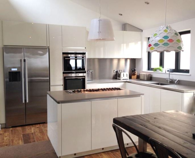 Gloss white handleless doors with a channel handle and matt grey composite worktop, in which a gas hob has been cleverly set into. Teamed with a shiny american fridge freezer  complimenting appliances. I really like that multi-coloured lampshade!