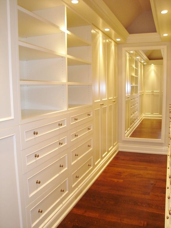 Narrow white closet with canned lights and wood floor